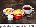 Baked omelet with golden crust in bowl with tea 43781283