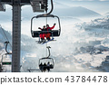 Couple snowboarders having fun on a ski lift in ski resort with beautiful background of snow-covered 43784478