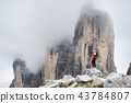 Climber on the high rocks background 43784807