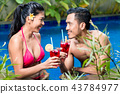 Couple having drinks in pool in Asia 43784977