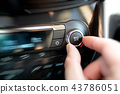 Man turning on car air conditioning system 43786051