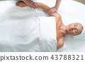 Smiling middle aged lady with towel on head having massage 43788321