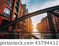 The red brick warehouse - Speicherstadt district in Hamburg Germany, framed by steel bridge arch 43794412