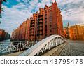 Arch bridge over canals in the Speicherstadt of Hamburg. Warm evening sun light on red brick 43795478