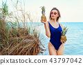 girl model in a monokini on the sea shore of a tropical island holding two pineapples 43797042