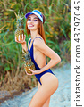 girl model in a monokini on the sea shore of a tropical island holding two pineapples 43797045