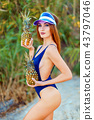 girl model in a monokini on the sea shore of a tropical island holding two pineapples 43797046