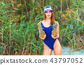 girl model in a monokini on the sea shore of a tropical island holding two pineapples 43797052