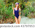 girl model in a monokini on the sea shore of a tropical island holding two pineapples 43797053