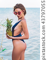 girl model in a monokini on the sea shore of a tropical island holding two pineapples 43797055