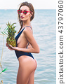 girl model in a monokini on the sea shore of a tropical island holding two pineapples 43797060