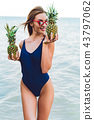 girl model in a monokini on the sea shore of a tropical island holding two pineapples 43797062