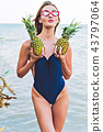 girl model in a monokini on the sea shore of a tropical island holding two pineapples 43797064