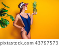 woman in swimwear isolated over yellow background holding pineapple. 43797573
