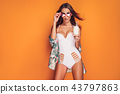 Woman in swimsuit holding beverage 43797863
