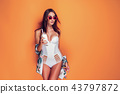 Woman in swimsuit holding beverage 43797872