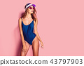 Woman in cap and swimwear looking away 43797903
