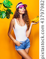 Woman in swimsuit and blue shorts holding banana and posing isolated over yellow background 43797982