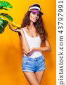 Woman in swimsuit and blue shorts holding banana and posing isolated over yellow background 43797991