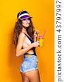 Sexy Woman in white swimsuit and blue jeans shorts, trendy visor holding beverage 43797997