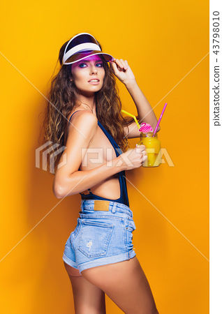 Sexy Woman in white swimsuit and blue jeans shorts, trendy visor holding beverage 43798010