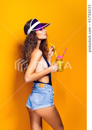 Sexy Woman in white swimsuit and blue jeans shorts, trendy visor holding beverage 43798035