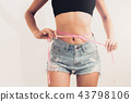 Slim woman measures her waist with measuring tape. 43798106