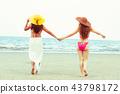 Happy women go sunbathing at sand beach in summer. 43798172