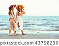 Happy women go sunbathing at sand beach in summer. 43798230