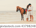 Young couple goes horse riding on tropical beach. 43798248