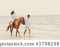 Young couple goes horse riding on tropical beach. 43798298
