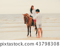 Young couple goes horse riding on tropical beach. 43798308