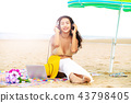 Plus size young woman sitting on the beach. 43798405
