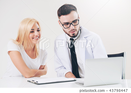 Male Doctor and Female Patient in Hospital Office 43798447