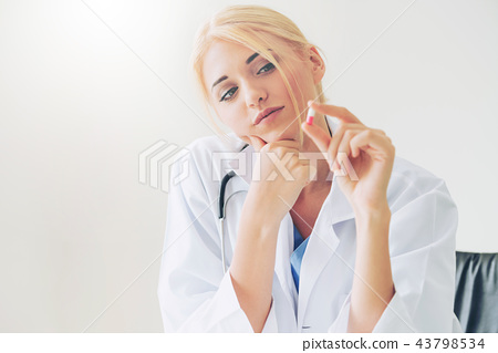 Young woman doctor holding a medicine pill in hand 43798534