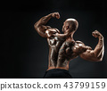 Unrecognizable muscular man with tattoo on back against of black background. Isolated. 43799159