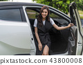 woman sitting in a car and open the door 43800008