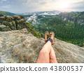 Legs in orange leather boots on mountain summit 43800537