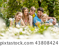 Family sitting on a meadow in summer or spring 43808424