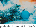 Blue Christmas tree ball next to the branch 43809629