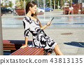 young business woman in a dress sitting on a bench and works on a tablet 43813135