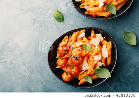 Tasty tomato pasta in bowls on blue table 43813379