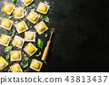 Raw ravioli with basil and flour on dark 43813437