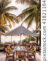Sea view dinner table under tropical coconut trees 43821164