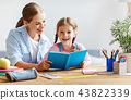 mother and child daughter doing homework writing and reading at 43822339
