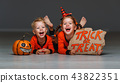 happy Halloween! cheerful children in costume with pumpkins on g 43822351