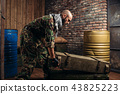 Terrorist in uniform loads boxes of ammunition 43825223