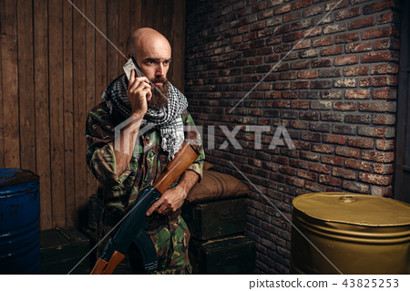 Terrorist holds rifle and mobile phone in hands 43825253