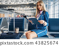 Stewardess reads magazine in airport waiting area 43825674