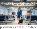 Stewardess with hand luggage going in airport hall 43825677